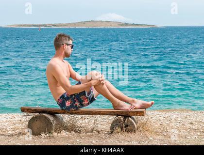 young shirthless man at the white rocky stones beach at Kamenjac National parc Porec Adriatic sea Pula Croatia - Stock Photo