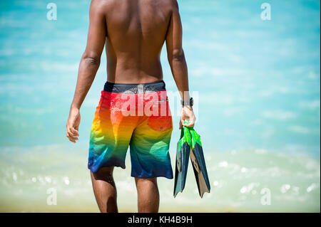 Unrecognizable young Brazilian body surfer walking with his fins along the shore at Arpoador beach, the popular - Stock Photo
