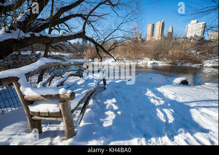 Scenic view of the Midtown skyline reflecting in the ice of the frozen Central Park lake the morning after a winter - Stock Photo
