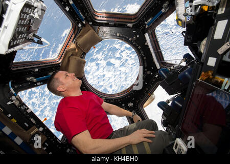 Expedition 52 Flight Engineer Jack Fisher photographed looking out of the International Space Station's Cupola windows. - Stock Photo