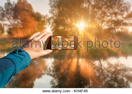 Photographing with smartphone in hand. Travel concept. Misty dawn on the river. - Stock Photo
