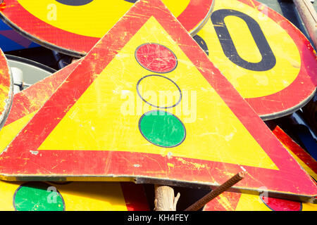 Used yellow industrial road signs with traffic lights or semaphore attention in the middle - Stock Photo