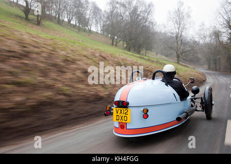 A Morgan three wheeler being driven through the British countryside. - Stock Photo