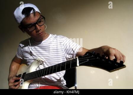 Photo of a teen playing an electric guitar - Stock Photo