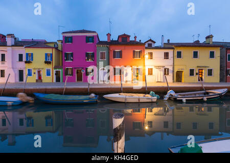 Fishermen's houses and small fishing boats reflected in the canal on Fondamenta della Pescheria, Burano in the Venetian - Stock Photo