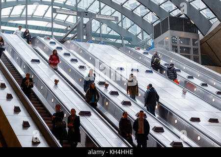 London, UK - November 24, 2017 - Entrance of Canary Wharf underground station with commuters on escalators - Stock Photo