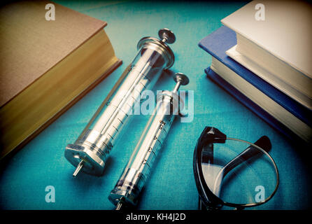 Several syringes vintage next to a few glasses and medical books - Stock Photo