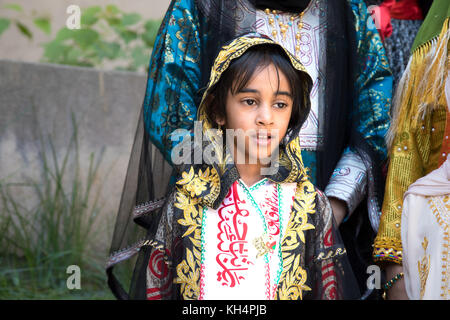 Portrait of a young Omani girl in the traditional Omani outfit. Nizwa, Oman. - Stock Photo