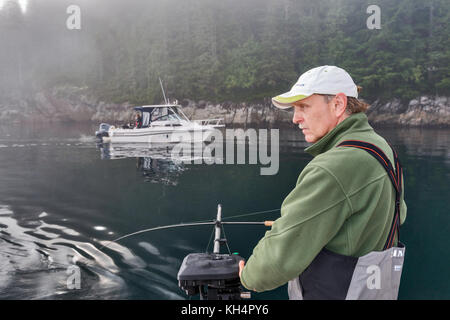 Middle-aged adult with fishing rod on boat, other boat passing, foggy morning in Johnstone Strait off Vancouver - Stock Photo