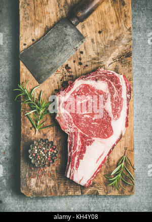 Raw prime beef meat dry-aged steak rib-eye and chopping knife - Stock Photo