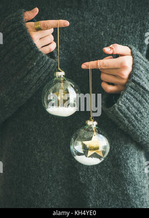 Woman in grey warm woolen sweater holding toy glass balls - Stock Photo