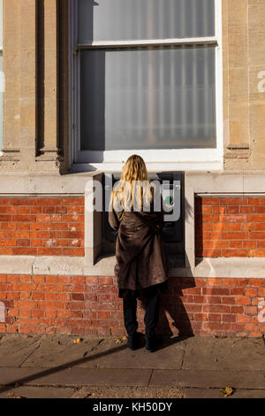 A blonde woman uses a cash machine outside of the NatWest bank on the High Street in Tenderden, Kent, UK - Stock Photo