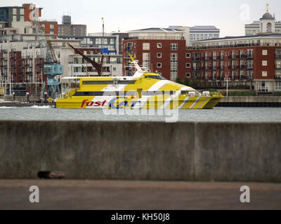 Yellow and white diagonal striped Fastcat ferry in Portsmouth Harbour, taken from Gosport - Stock Photo