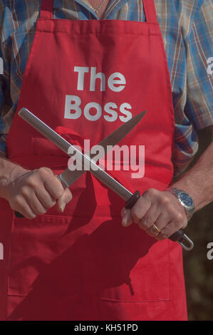 Man wearing 'The Boss' apron sharpening knife with a steel - Stock Photo