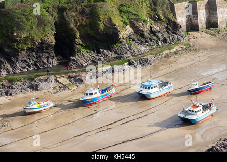 Beached fishing boats on the sand at low tide in the harbour at the North Cornwall seaside village of Port Isaac, - Stock Photo