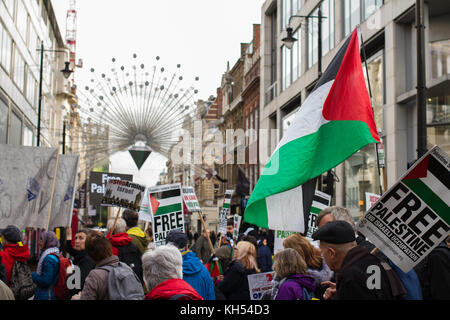 Protestors for Palestinian rights march past the Oxford Street Christmas lights on the centenary of the Balfour - Stock Photo
