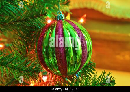 A shot of a Green and Red Christmas Bulb closeup thats bright and colorful on a Christmas Tree with a brown back - Stock Photo