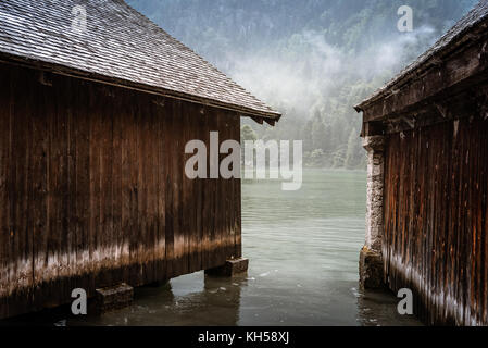 Wooden cottages in Konigssee lake a misty summer day - Stock Photo