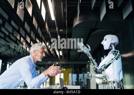 Mature businessman or a scientist with robot. - Stock Photo