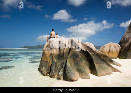 The Seychelles, La Digue, L'Union Estate, tourists sat on rocks at Anse Source d'Argent beach - Stock Photo