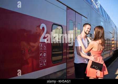 Happiness of  young caucasian couple seeing each for the first time. They are standing next to the train, wearing - Stock Photo
