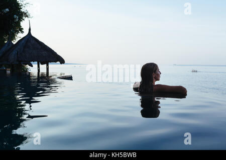Black silhouette of happy woman on summer beach holiday relaxing in luxury spa hotel in infinity swimming pool with - Stock Photo