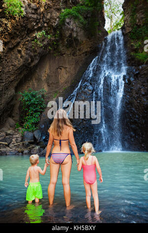 Mother, kids swim in water pool under waterfall in jungle canyon. Travel adventure, hiking activity with child. - Stock Photo