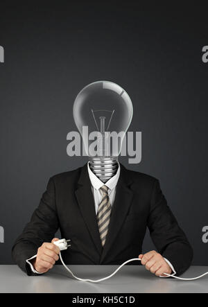 Businessman with light bulb head and plug, switch ideas creative concept on black - Stock Photo