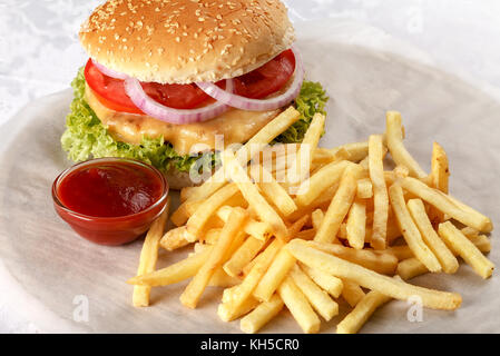 Fresh cheeseburger with French fries and tomato sauce. Close-up - Stock Photo