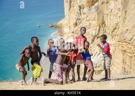 CAOTINHA, BENGUELA, ANGOLA - MAY 11 2014: Group of young African boys posing in front of spectacular desert coast - Stock Photo