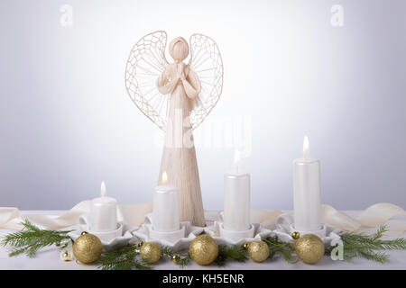 A white angel and four white Advent candles, Christmas tree branches are decorated with golden balls. The imminent - Stock Photo