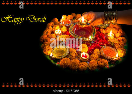 Diwali festival background concept with clay diya lamps floral decorations and rangoli pattern. - Stock Photo