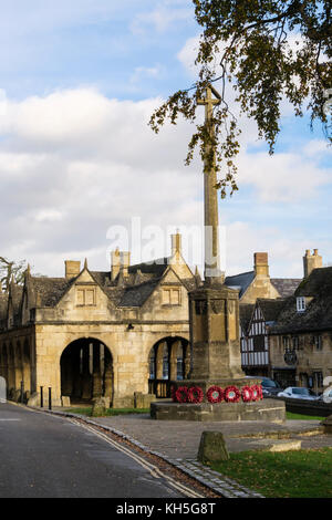 War memorial with poppy wreathes by old 17th century Market Hall in historic Cotswolds village. Chipping Campden - Stock Photo