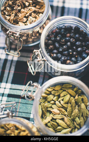 Whisky and Gin Ingredients: in glass jar on blue and white tartan - Stock Photo