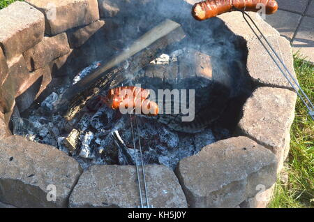 Two boys are grilling or barbecuing Polish sausages over an open fire pit in their backyard - Stock Photo