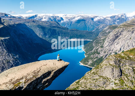 Person sitting on the edge of Trolltunga rock formation, Norway, with a spectacular view on Ringedalsvatnet. - Stock Photo