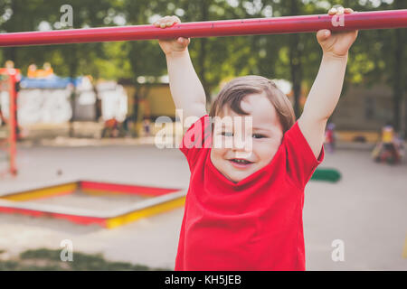portrait of cute boy smiling and playing on playground - Stock Photo