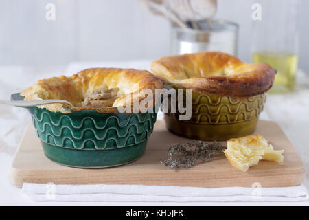 Chicken pie with mushrooms, cooked in individual ceramic forms. Rustic style, selective focus. - Stock Photo