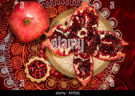 Top view of peeled pomegranate and ruby grains in a bowl on  oriental tablecloth Stock Photo