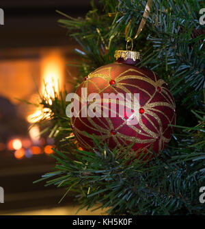 Red Christmas Ball on a tree with fireplace in background - Stock Photo