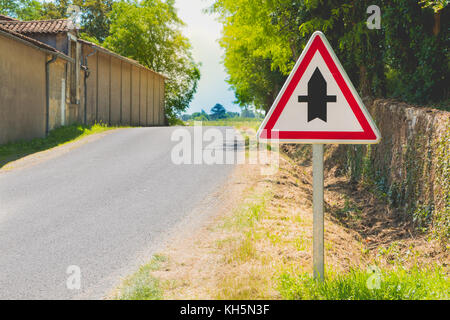 country road with a priority crossroads sign in france - Stock Photo