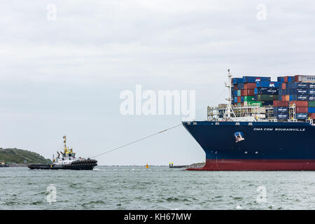 ROTTERDAM, THE NETHERLANDS - JUNE 12, 2017: A tug boat brings the ultra large container ship CMA CGM Bougainville - Stock Photo