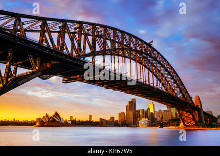 Sunrise at Harbour Bridge and Sydney Opera House, Milsons Point, Sydney, New South Wales, Australia - Stock Photo