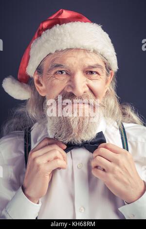 New year, Santa Claus adjusting bow tie. - Stock Photo