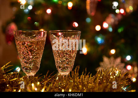 Decorative holiday background with champagne glasses on a background of a Christmas tree with toys and lights - Stock Photo