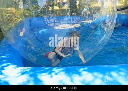 Cheerful 9 -year-old girl inside a transparent ball-zorb - Stock Photo