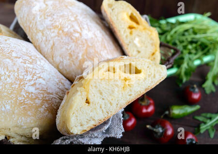 Ciabatta with cheese stuffing - freshly baked Italian white bread on a dark wooden background. For the preparation - Stock Photo