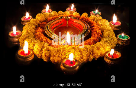 Diwali clay diya lamps with floral decorations in dark background - Stock Photo