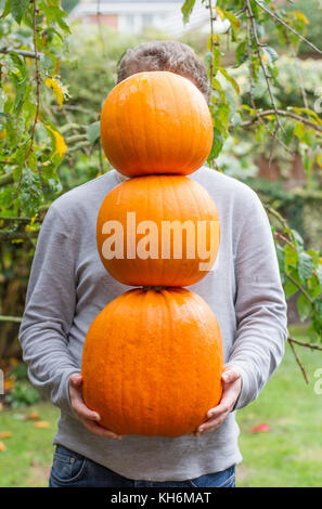 An anonymous young man holding and balancing three pumpkins in his hands that are covering his face in an outdoors - Stock Photo