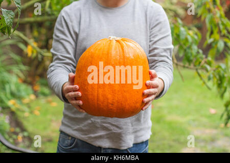A young man standing outdoors in a garden and holding a large pumpkin in his hands in a mid section shot - Stock Photo